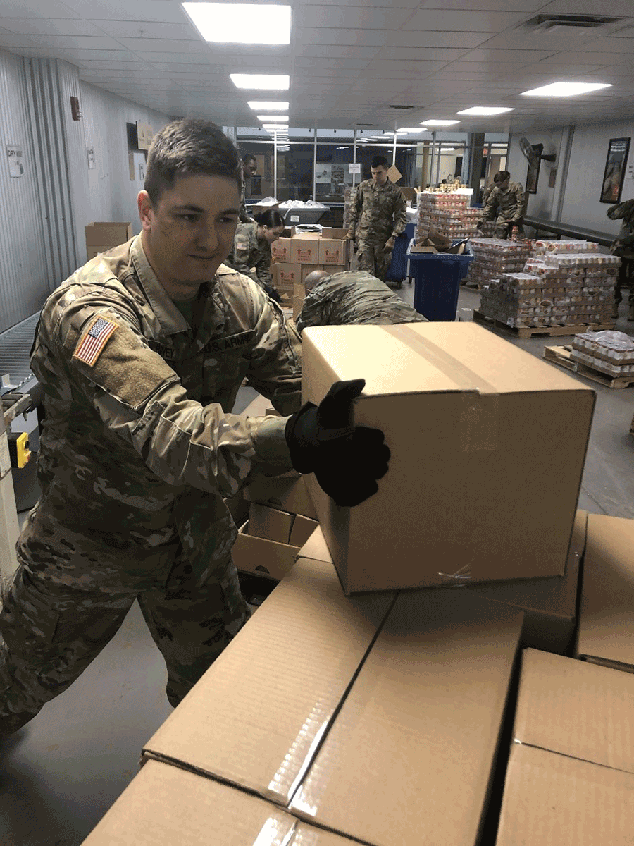 Soldiers loading boxes in warehouse.