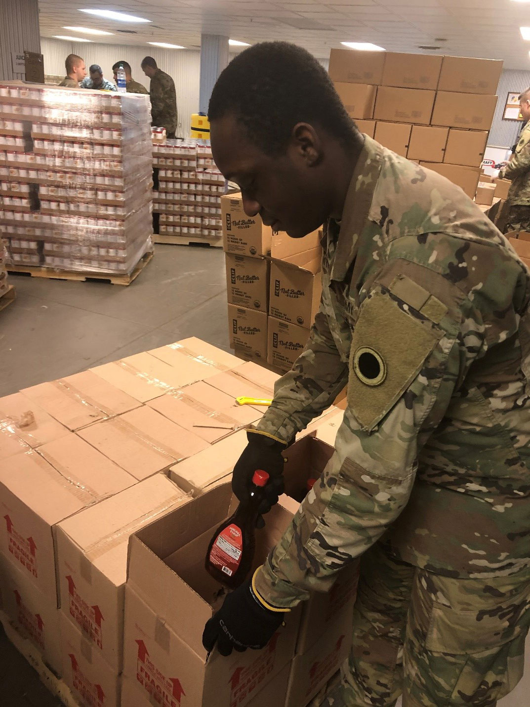 Soldier loads syrup into box.