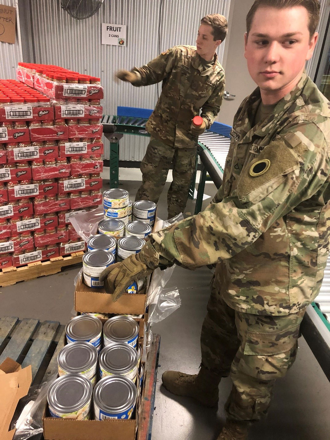 Soldier unloads canned chicken from boxes.