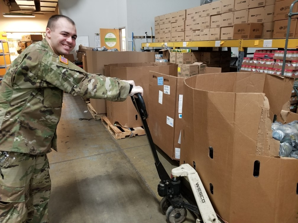 Soldier loads box of canned goods with dolly.