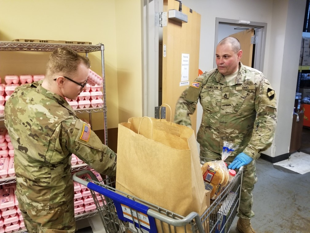 Soldiers load grocery cart.