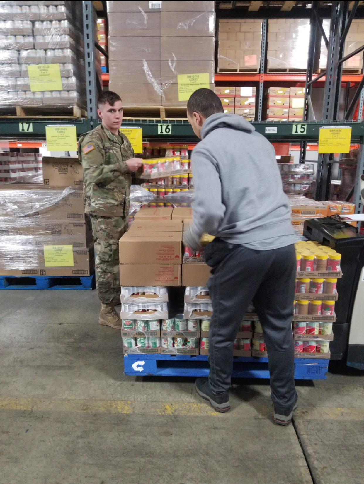 Soldier helps repack diapers for distribution .