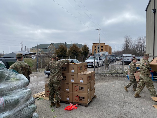 Soldiers unload pallet of apple boxes.