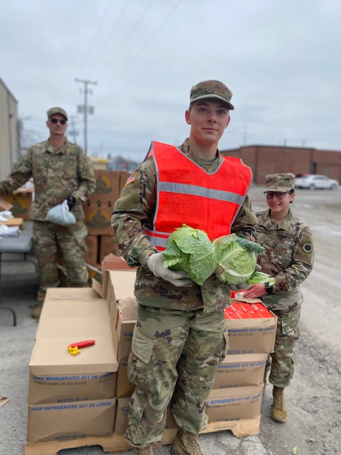 Soldiers unload cabbage.