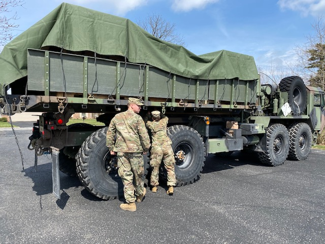Soldiers prepare to unload trailer from truck.