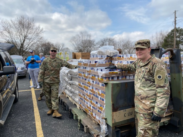 Soldiers stand by pallets of produce and canned goods.