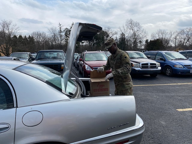 Soldier loads box into trunk.