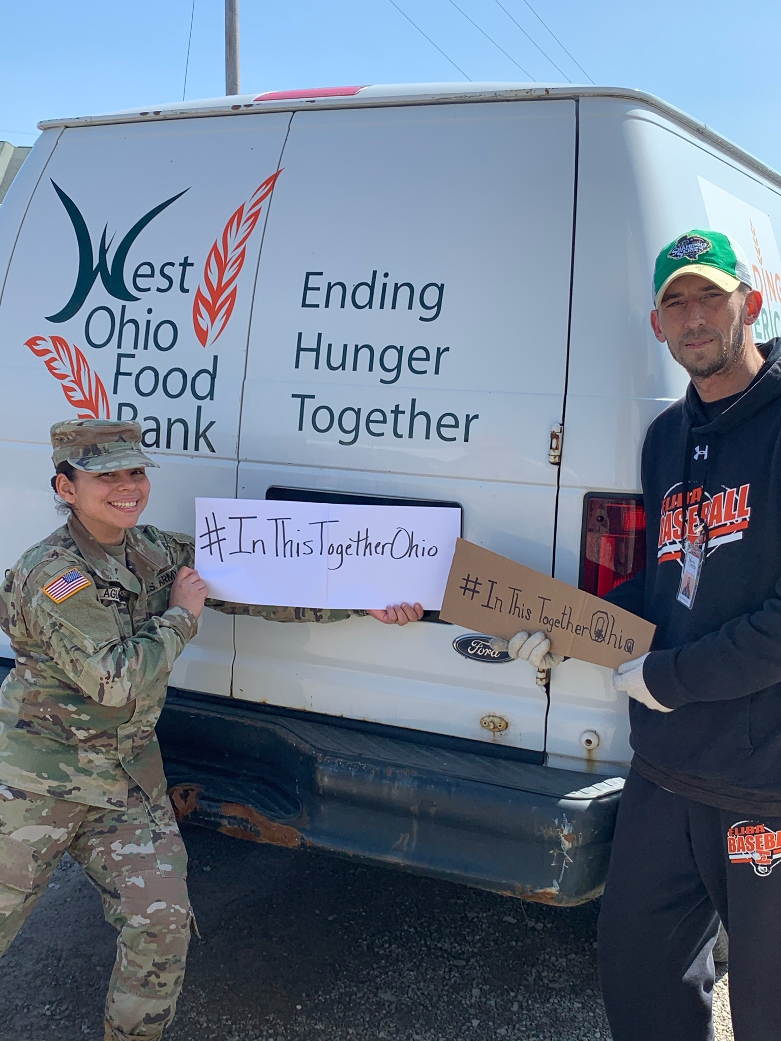 Soldier and man hold signs that  read #In ThisTogetherOhio behind food truck.