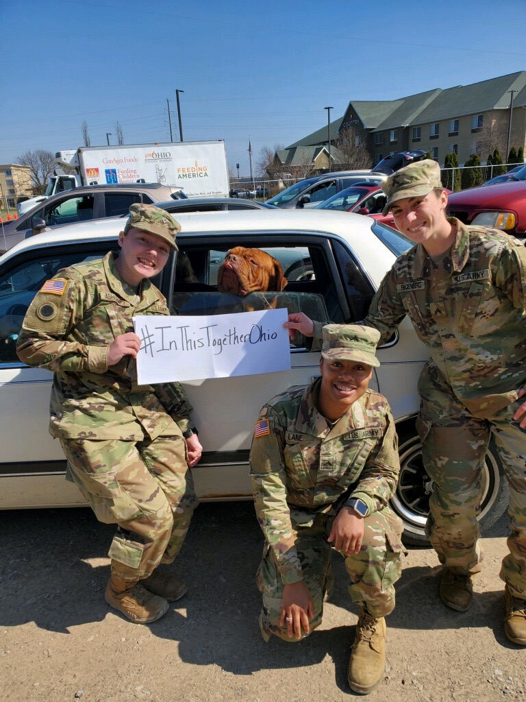 Soldiers stand outside of car in drive through with #InThisTogether signs.