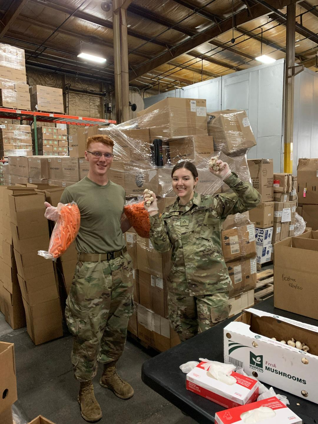Soldiers load  boxes with produce.