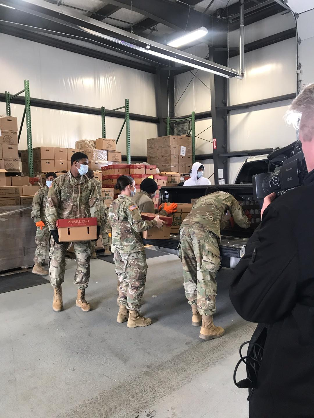 Soldiers load  boxes into truck inside warehouse.