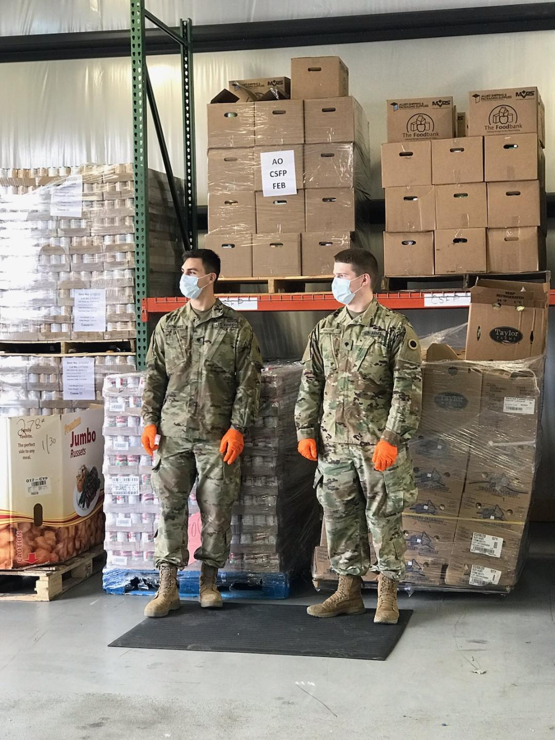 Soldiers standing in front of pallets with masks and gloves.