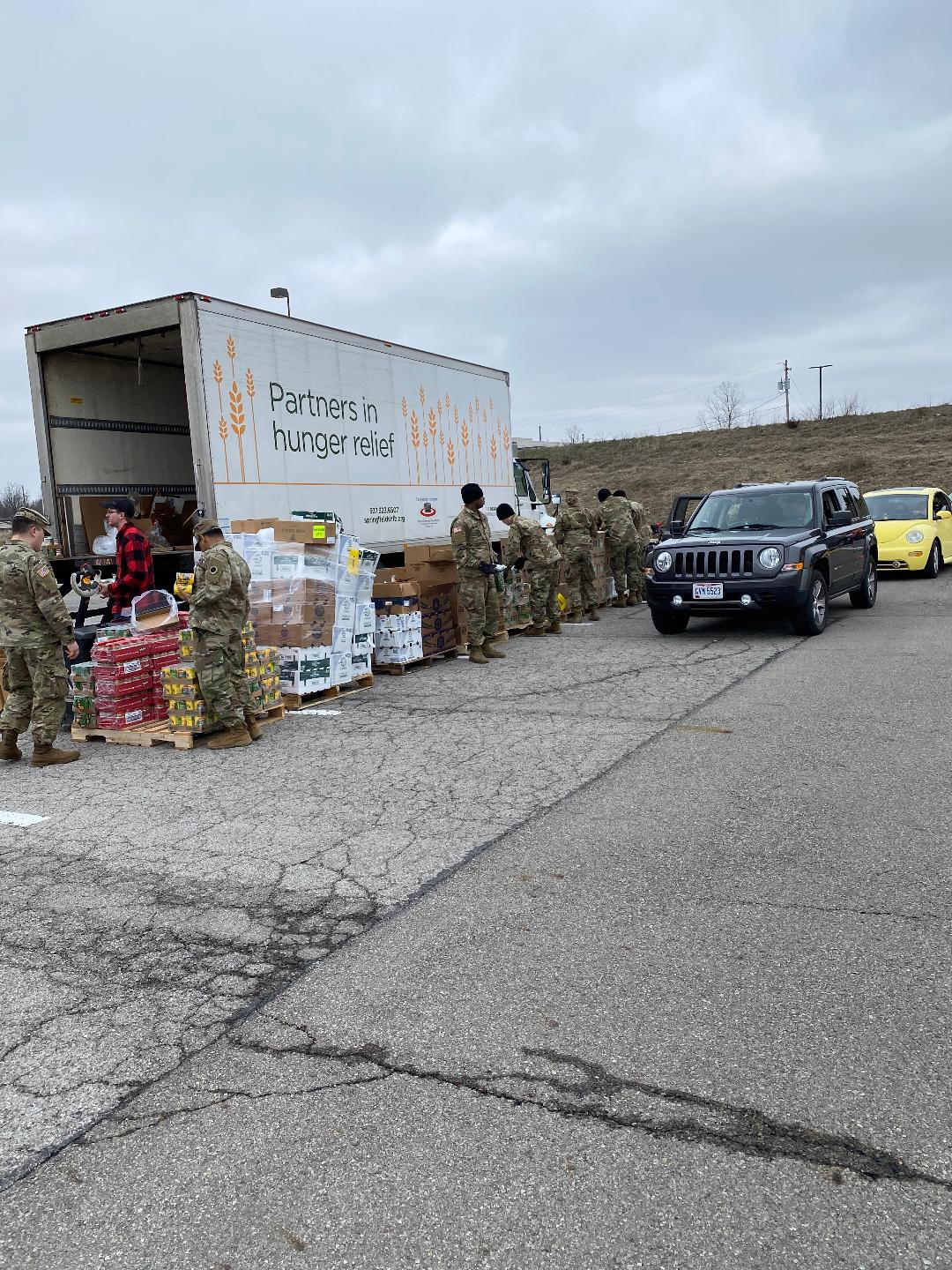 Soldiers pass out supplies from the Partners in Need semi to cars in drive through.