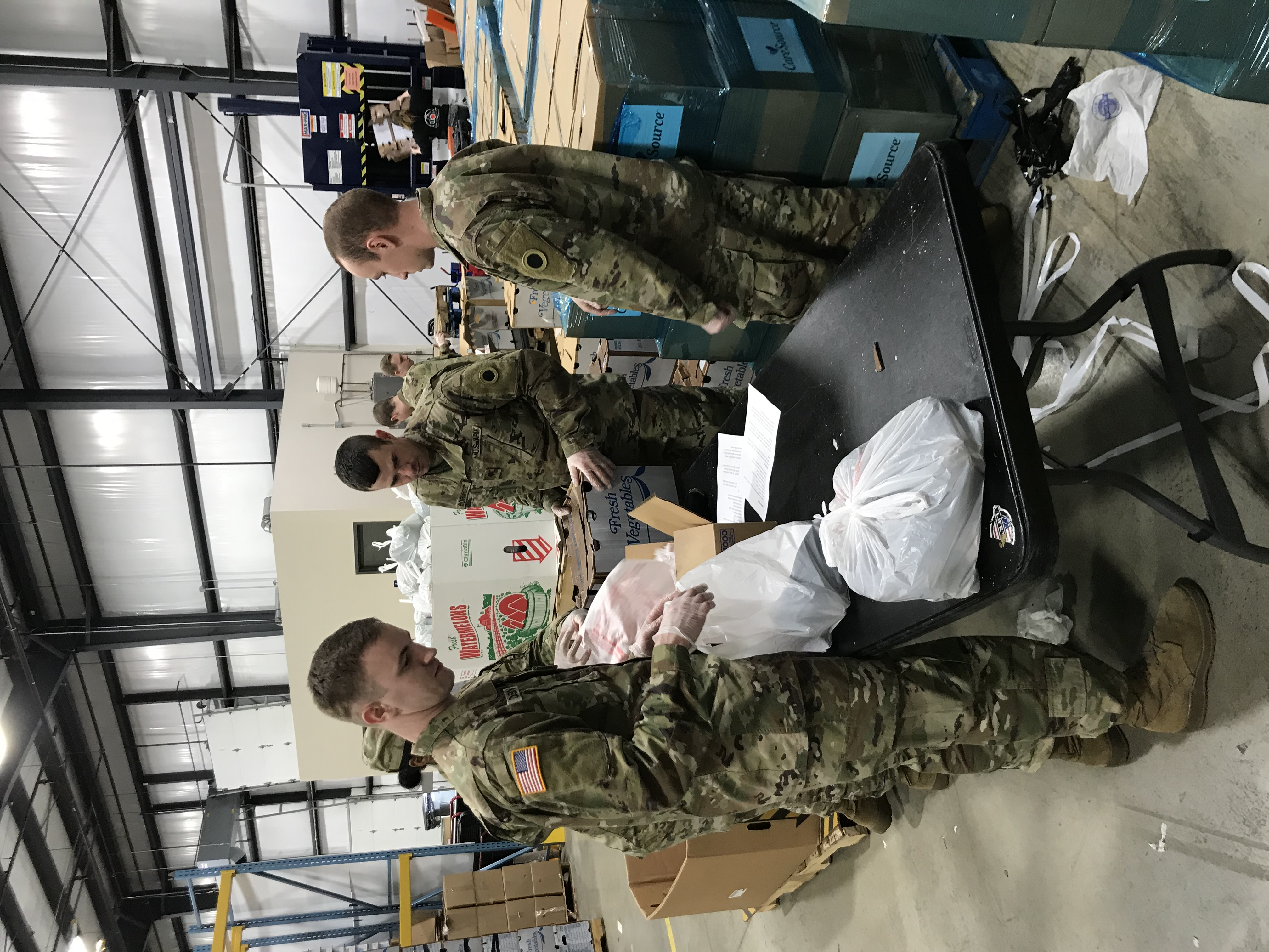 Soldiers package produse at table inside warehouse.