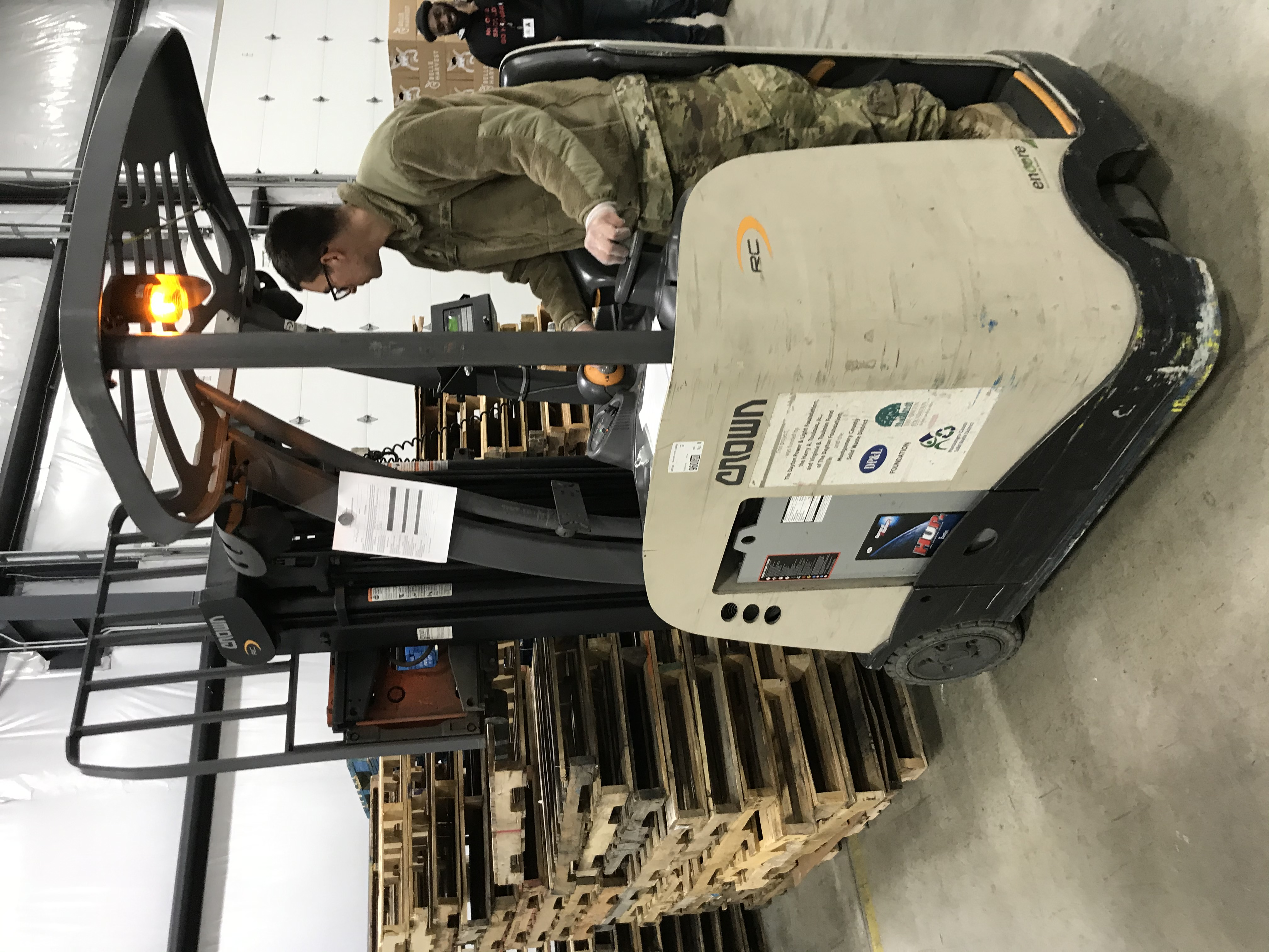 Soldier moves pallets inside warehouse.