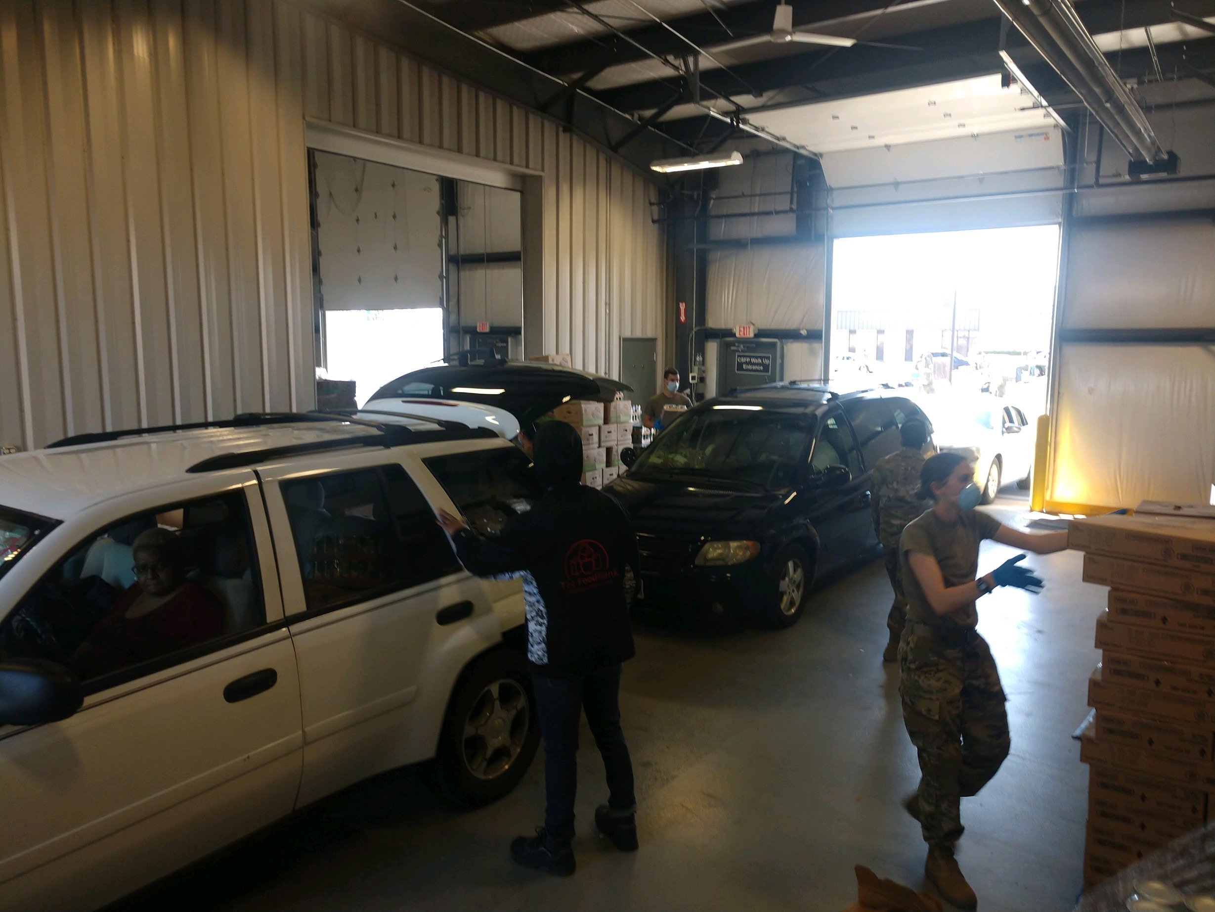 Soldiers load boxes into cars.