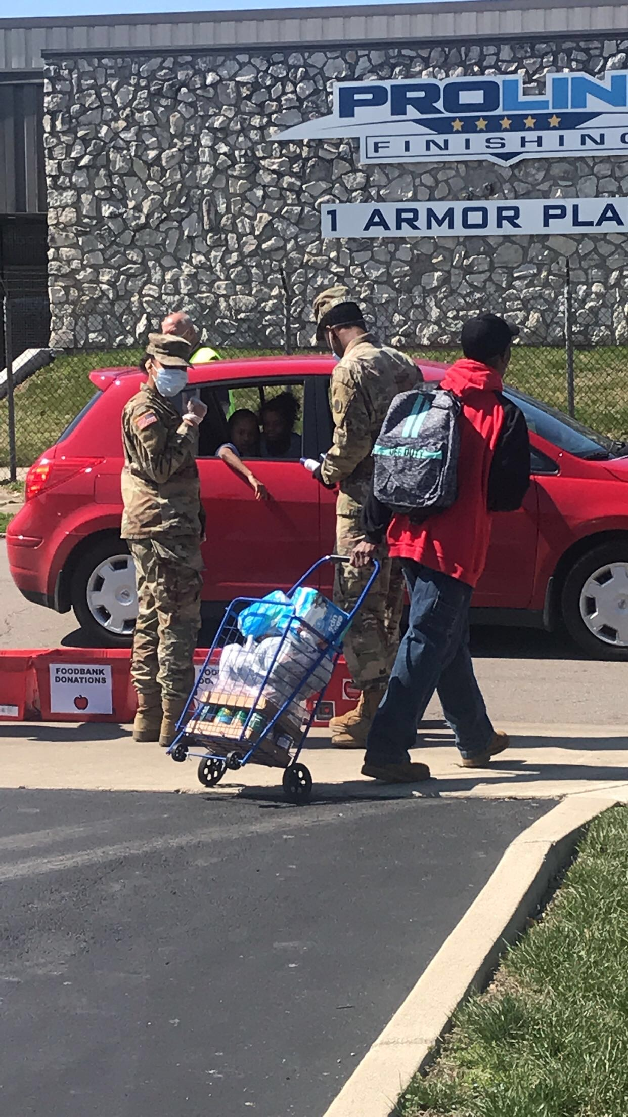 Soldiers hand supplies to cars curbside.