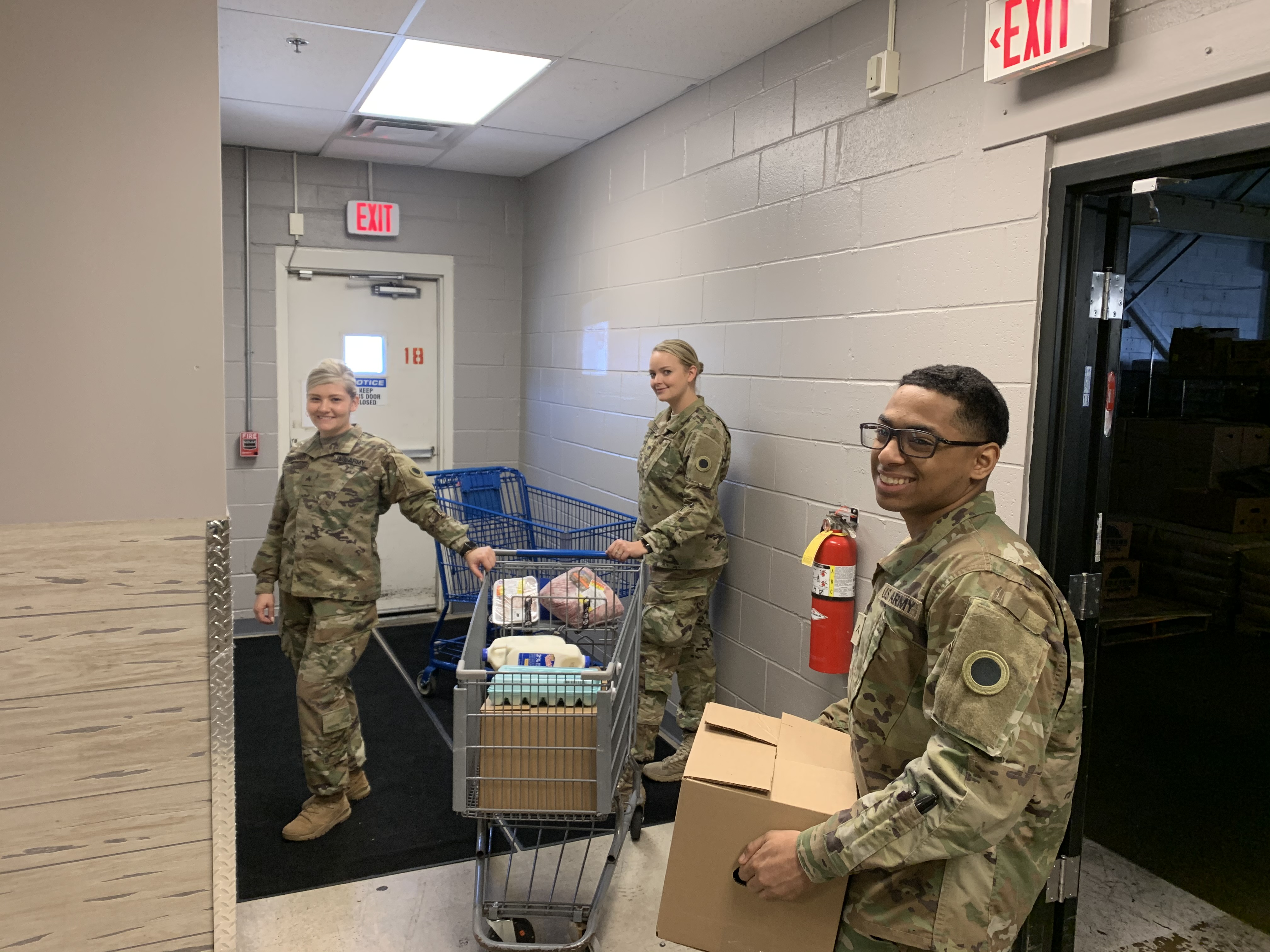Soldiers pack carts in warehouse.
